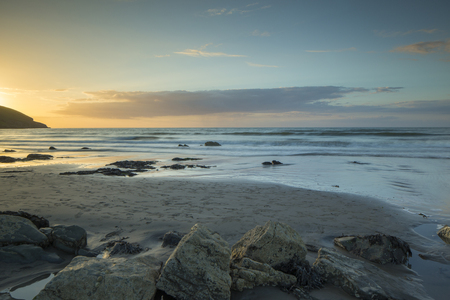 sunset of the tide coming right up to the camera on a beautiful beach in wales, UK Stok Fotoğraf