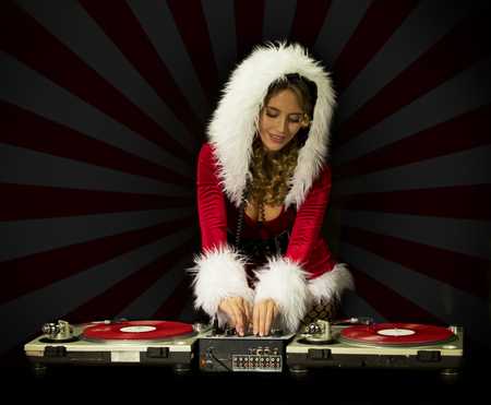 beautiful blonde women DJ in cute santa claus costume for christmas time disco shoot. Turntables