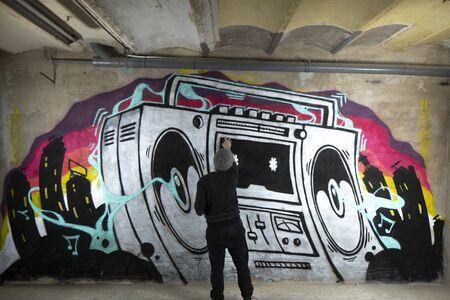 un graffii artist spruzza l'opera d'arte di un boom box ghettoblaster su un muro Archivio Fotografico