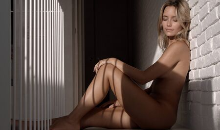 beautiful naked woman seated agaisnt a wall posing in lovely late afternoon light
