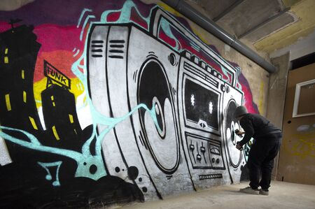 a graffii artist sprays art work of a boom box ghettoblaster on a wall