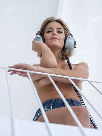 beautifu topless woman posing with headphones, in luxury white space