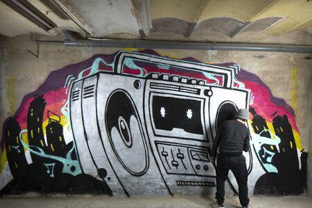 un graffii artist spruzza l'opera d'arte di un boom box ghettoblaster su un muro