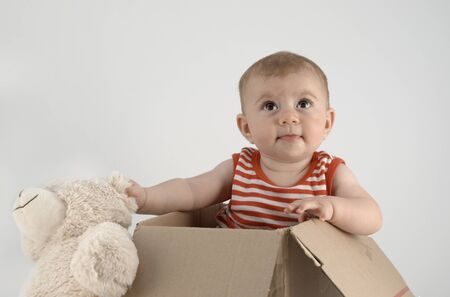 adorable small baby girl in a box with cuddly teddy bears Stock Photo