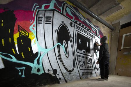 a graffii artist paints an art work of a boom box ghettoblaster on a wall