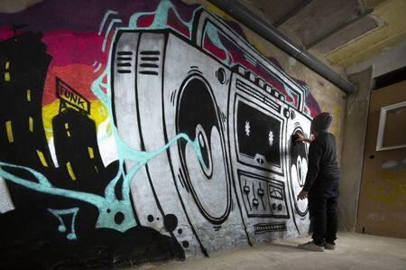 un artista di graffiti dipinge un'opera d'arte di un boom box ghettoblaster su un muro Archivio Fotografico