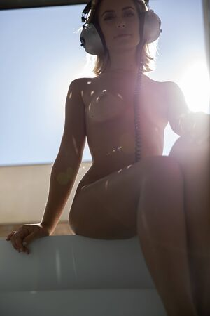 beautiful naked woman seated with headphones, backlit agaisnt the afternoon sun Stock Photo