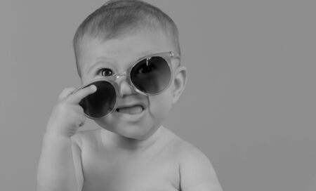 adorable small baby girl holding sunglasses, against plain colour background