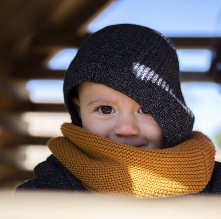 adorable small baby girl with expressive face wrapped up for autumn Stock Photo