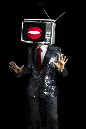 cool male performer with a television as a head. the tv lips on the screen and the man is dancing