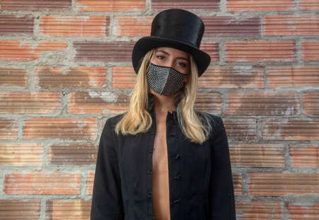 Young woman wearing sparkly black face mask against brick wall