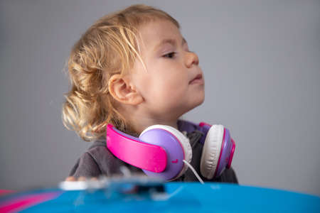 Baby girl wearing headphones with record player