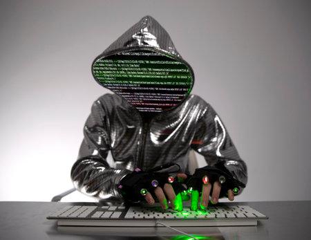 Computer hacker in silver jacket 스톡 콘텐츠