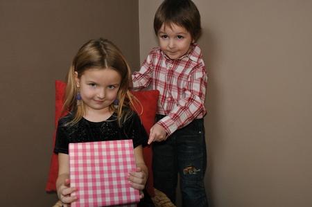 Girl with boy open gift box photo