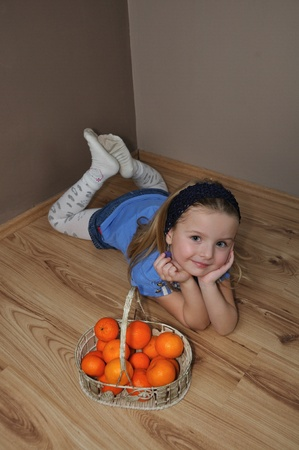 Girl with fruit basket on the wooden ground photo