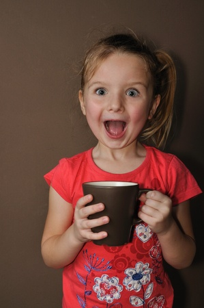 Suprised girl with brown cup Standard-Bild