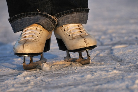 Closeup woman legs in white ice skates photo