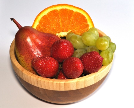 Isolated mix of strawberries, orange slice, pear and grapes in wooden dish Stock Photo - 13536566