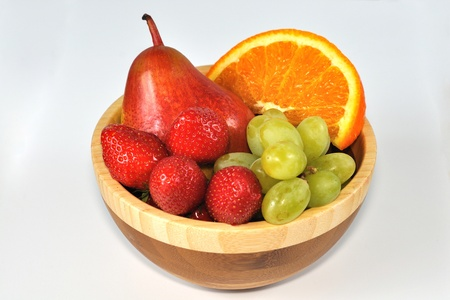 Isolated mix of strawberries, orange slice, pear and grapes in wooden dish Stock Photo - 13536561
