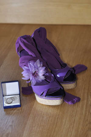 Violet heels with flower and wedding rings on wooden floor photo