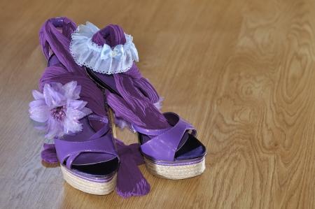 Violet heels with flower and garter  on wooden floor photo
