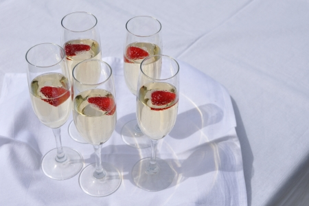 champain: Glasses with champain and strawberries on white tray Stock Photo