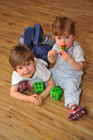 Happy siblings are together on wooden floor with toys photo