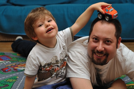 Son and father playing with cars on carpet at home Standard-Bild