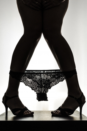 Silhouette of beautiful young woman legs on high heels with laced pinties photo