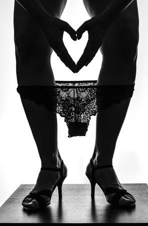Silhouette of beautiful young woman legs on high heels with laced pinties and heart from hands photo