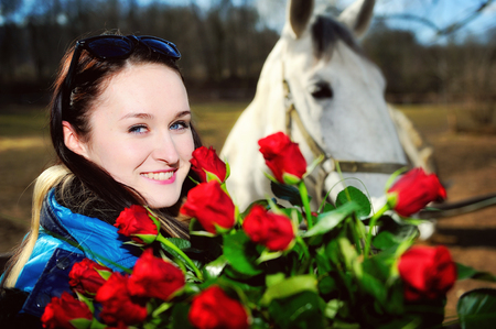 animal sexy: Beautiful young woman standing with bunch of roses before white horse