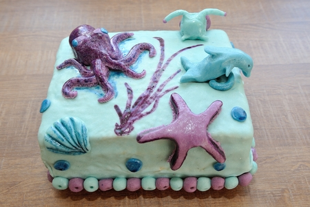 Beautiful birthday cake in submarine decoration with dolphin, octopus, snail and underwater star photo