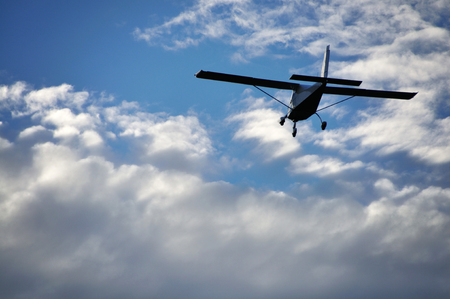 Small plane in the air. Blue sky with white clouds.