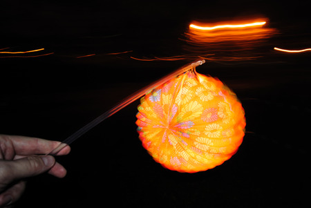 Lighting paper lantern in hand with illusion of motion and flame