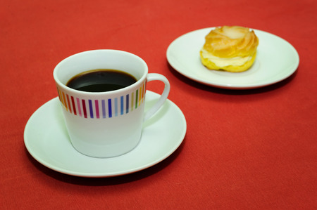 stimulate: cup of coffee with cream puff on white plate Stock Photo