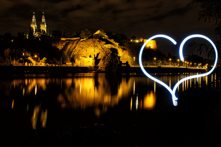 light painting: Vysehrad with Basilica of St Peter and St Paul in Prague from Vltava river side with big hearth created by light painting. Czech Republic. Famous tourist destination beatifully lighted in the night.