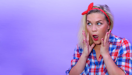 topknot: Blond girl with blue eyes and retro fashion style looking suprised to left empty space with open mouth and emotional gesture. Red topknot with white dotted in hair and checked shirt.