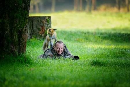 Wildlife photographer hidden in grass with big smile in face, having curious fox on his back looking down to the photographer