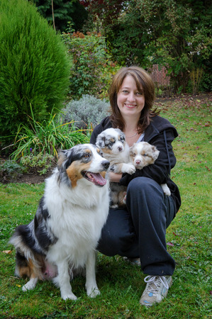 breeder: White young woman dog breeder with sitting Australian Shepherd adult female dog and her puppies in arms outside on garden