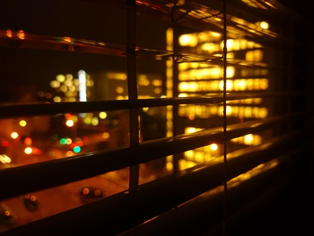 office window view: Closeup of shutter at night in office building  with view to lighten city