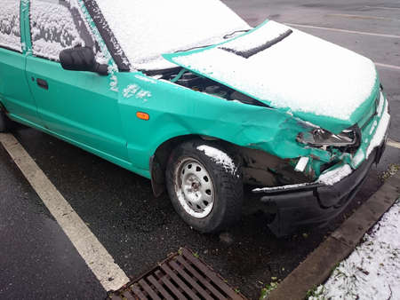Crashed car on parking place. Green wreck under dusting of snow.