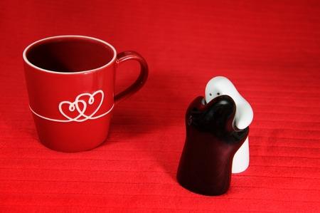 desayuno romantico: Amor, beso y un abrazo con el coraz�n en la taza, salero y pepperer sobre fondo rojo. Foto de archivo