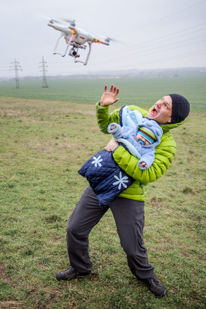 panicky: Man protects his baby against an attacking drone. Dangerous  drone closeup to frightened parent with infant in arms Stock Photo