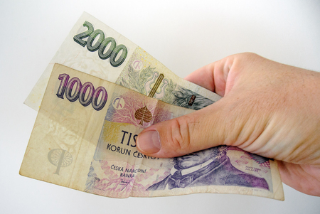 pay bills: One thousand and two thousand czech crown bank-notes in white man hand. Pay bills with money. Currency concept