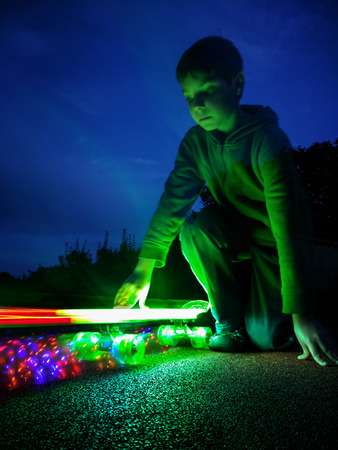 Young boy kneels and holding lighting skateboard before motion on long exposure