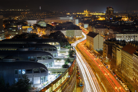 Prague from beauty bird perspective. Modern urban Prague part with old town in background. Cityscape to highway full of car lights Standard-Bild