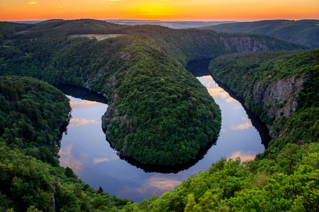 Beautiful sunset landscape view to Czech Republic river Vltava, close to Prague. Orange sky during summer with clouds reflection in the water. 스톡 콘텐츠