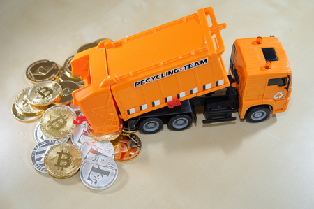 Spill waste cryptocurrency from dumpster car. Conceptul image to cryptocurrency bubble