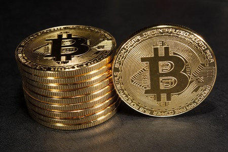 Column of bitcoins with one single coin next to them Zdjęcie Seryjne
