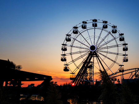Ferris wheel in sunset.  Big wheel with cabins. Circle construction to beautiful panoramatic view. Summer  amusement ride for enjoy holidays.